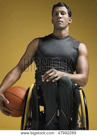 Portrait of a confident paraplegic athlete in wheelchair holding basketball against yellow background