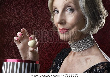 Closeup portrait of a wealthy senior woman with box of candy