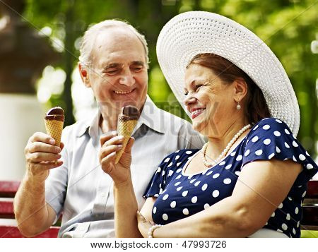 Happy old couple eating ice-cream outdoor.