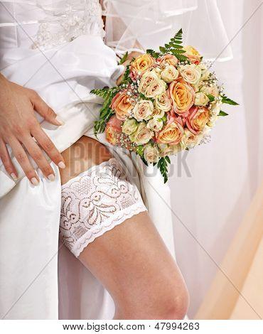 Garter at leg of bride and flower bouquet.