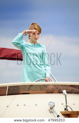 Fashion woman with steering wheel showing thumb up on the yacht