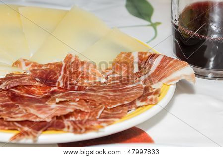Typical Spanish Tapa With Slices Of Serrano Ham And Manchego Cheese, Accompanied With A Glass Of Rio