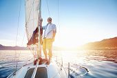 stock photo of sails  - sunrise sailing man on boat in ocean with flare and sunlight on calm morning on the water - JPG