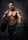Muscular Man With Two Metal Fuel Cans Indoors
