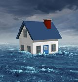 stock photo of economics  - House flood insurance concept with a generic residential home damaged during a flooding disaster by severe weather or hurricane causing environmental damage and economic hardships affecting the real estate industry - JPG