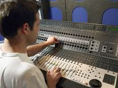 Young male sound technician in recording studio