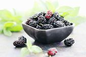 stock photo of mulberry  - Ripe black mulberry on a black plate - JPG