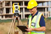 stock photo of theodolite  - mid age land surveyor working at construction site with theodolite - JPG