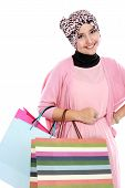 stock photo of fitri  - Happy young muslim woman with shopping bag isolated over white background - JPG