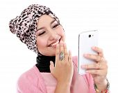 stock photo of fitri  - Portrait of a laughing beautiful muslim woman texting with her smartphone isolated over white background - JPG