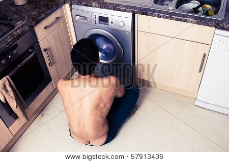 Young Man Watching The Wash Cycle