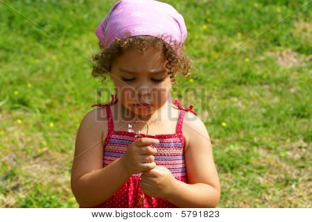 Sad Little Girl Looking at Flower