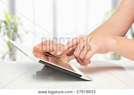White Tablet With A  Blank Screen In The Hands On Table