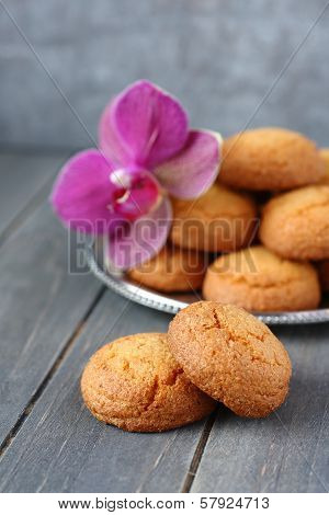 Almond Cookies With Orchid Flower On Rustic Wooden Table
