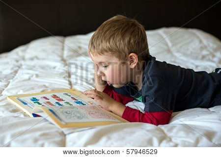 A young blonde boy is learning on a bed