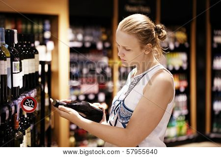 Woman reading inscription on the wine bottle in store