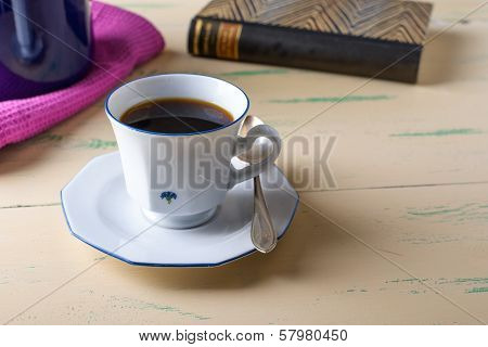 Coffee Cup On Wood Table With A Book In The Background