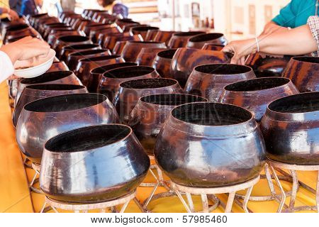 Many People Coin Down To Monk's Alms Bowl In Thai Temple
