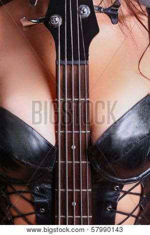 guitar fretboard sandwiched between her breasts