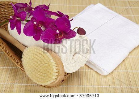 Bath Brush And Rolled Towel In A Basket