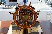 stock photo of ship steering wheel  - Vintage wooden steering wheel and navigation compass on a tall sailing ship - JPG