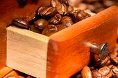 image of wooden box from coffee mill  - Grains of black roasted coffee in drawer of mill - JPG