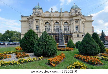 KRAKOW, POLAND - SEPTEMBER 15, 2013: Monument to Aleksander Fredro against the Juliusz Slowacki Theatre. Erected in 1893, the theater named after Polish poet Juliusz Slowacki in 1909
