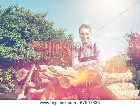 Handsome guy in Lederhosen posing outside in nature