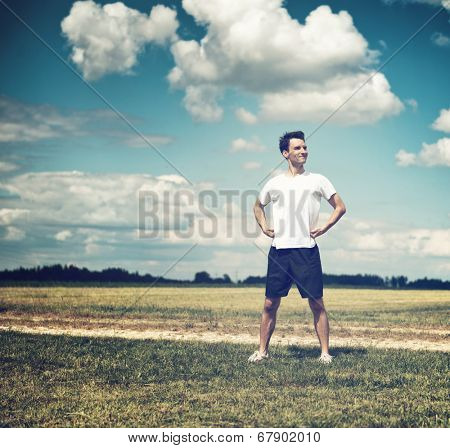 Fit handsome young male athlete pausing during his daily workout to admire the countryside standing against sky with his hands on his hips and a pleased smile