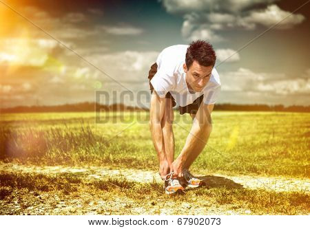 Athlete pausing on a rural track in green open countryside to tie his laces on a morning run as he does his training and workout to keep fit and healthy with a glowing sun behind him