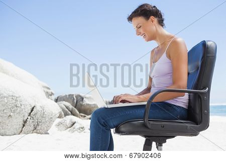Pretty brunette using laptop on the beach sitting on swivel chair on a sunny day
