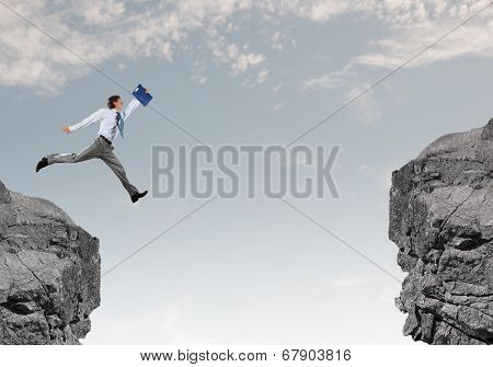 Young businessman with suitcase jumping over mountain gap
