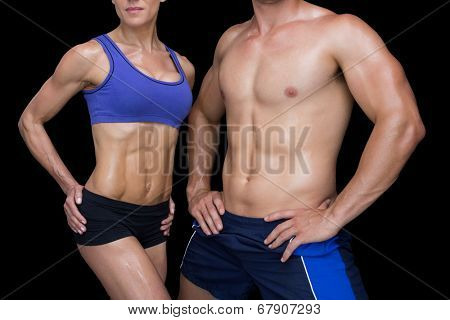 Crossfit couple posing with hands on hips on black background