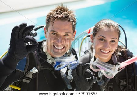 Smiling couple on scuba training in swimming pool showing ok gesture on a sunny day