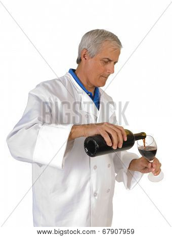 winemaker/enologist pouring red wine into a glass, to sample his work isolated on white.