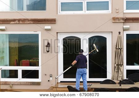 Professional window washer cleaning house windows with de-ionized water using an extension pole