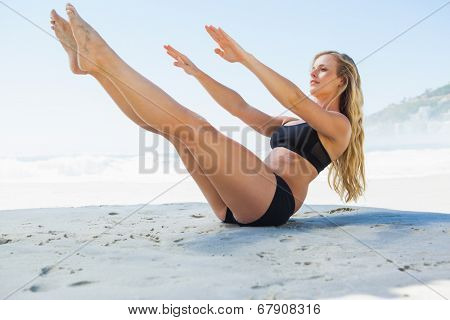 Fit blonde in core balance pilates pose on the beach on a sunny day