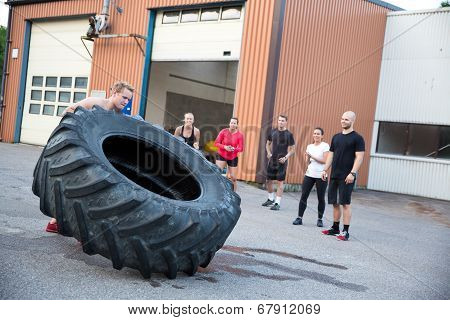 Man flipping heavy tires outdoor as workout