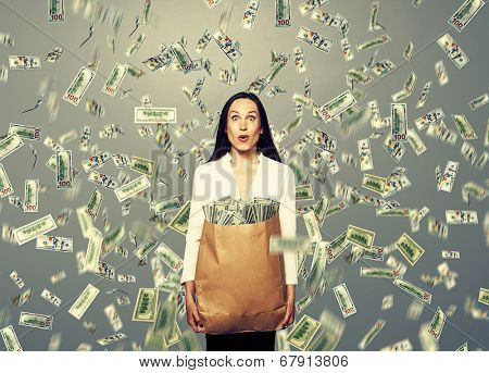 surprised young businesswoman holding paper bag with money under dollar's rain