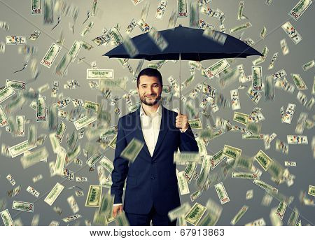 smiley glad businessman with umbrella standing under money rain