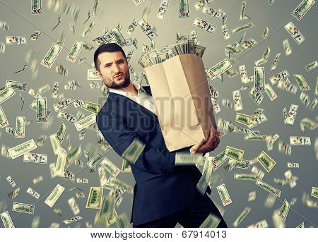 handsome successful businessman holding heavy paper bag with money under dollar's rain