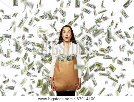 amazed young businesswoman holding paper bag with money under dollar's rain
