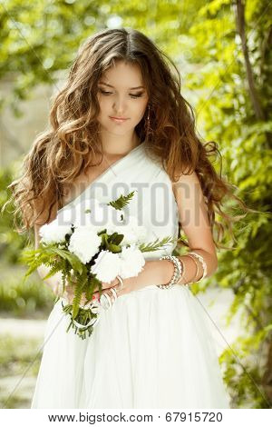 Beautiful Young Bride Holding Bouquet Of Spring Flowers With Wedding Makeup And Long Wavy Hair Style