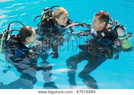 Smiling friends on scuba training in swimming pool on a sunny day