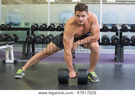 Shirtless bodybuilder lifting heavy black dumbbell in a lunge at the gym