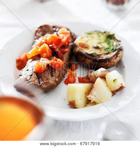 steak covered in tomatoes with potatoes