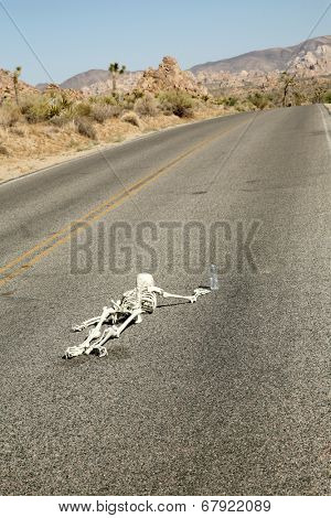 A lost hiker dies of thirst on a deserted desert road inches away from a bottle of water.  Dark Humor Series.