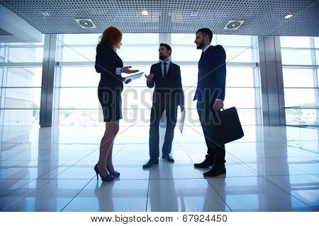 Group of three white collar workers interacting on background of office window