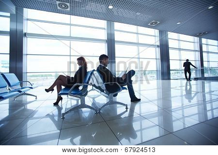 Two business partners reading at the airport on background of their colleague by the window