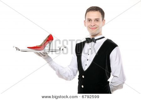 Young butler holding a tray with a high heel on it